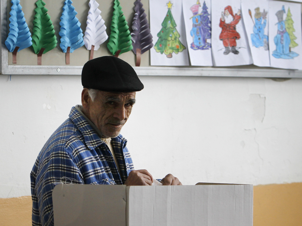 A man folds his ballot before voting at a polling station in village of Tearce, in northwestern Macedonia, on Sunday, Dec. 25, 2016. Au...