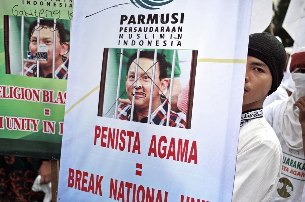"A Muslim man displays a poster during a protest against Jakarta Governor Basuki ""Ahok"" Tjahaja Purnama outside the North Jakarta Court ..."