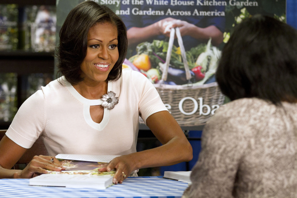 """FILE - In this June 12, 2012, file photo, first lady Michelle Obama signs copies of her book """"American Grown: The Story of the White Ho..."""