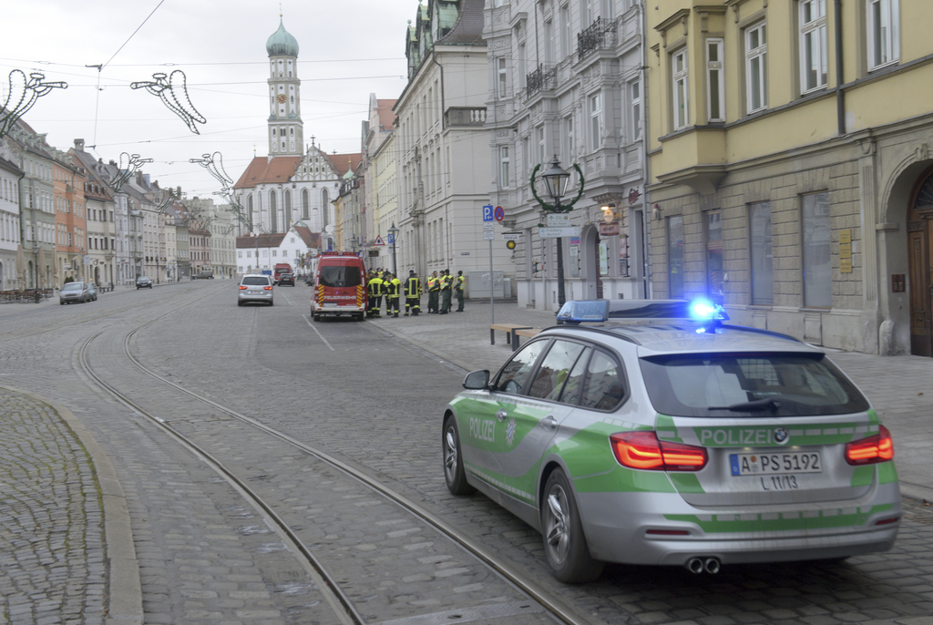 A police vehicle driving through an almost empty street in Augsburg, Germany, Sunday Dec. 25, 2016. Thousands of people in the German t...