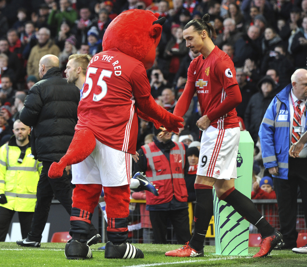 Manchester United's Zlatan Ibrahimovic, right, is welcomed on the pitch by club mascot during the English Premier League soccer match b...