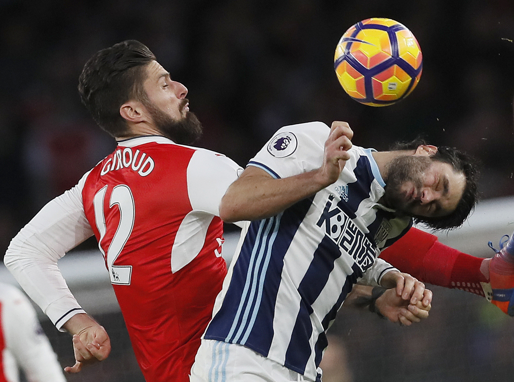 Arsenal's Olivier Giroud, left, vies for the ball with West Brom's Claudio Yacob during the English Premier League soccer match between...