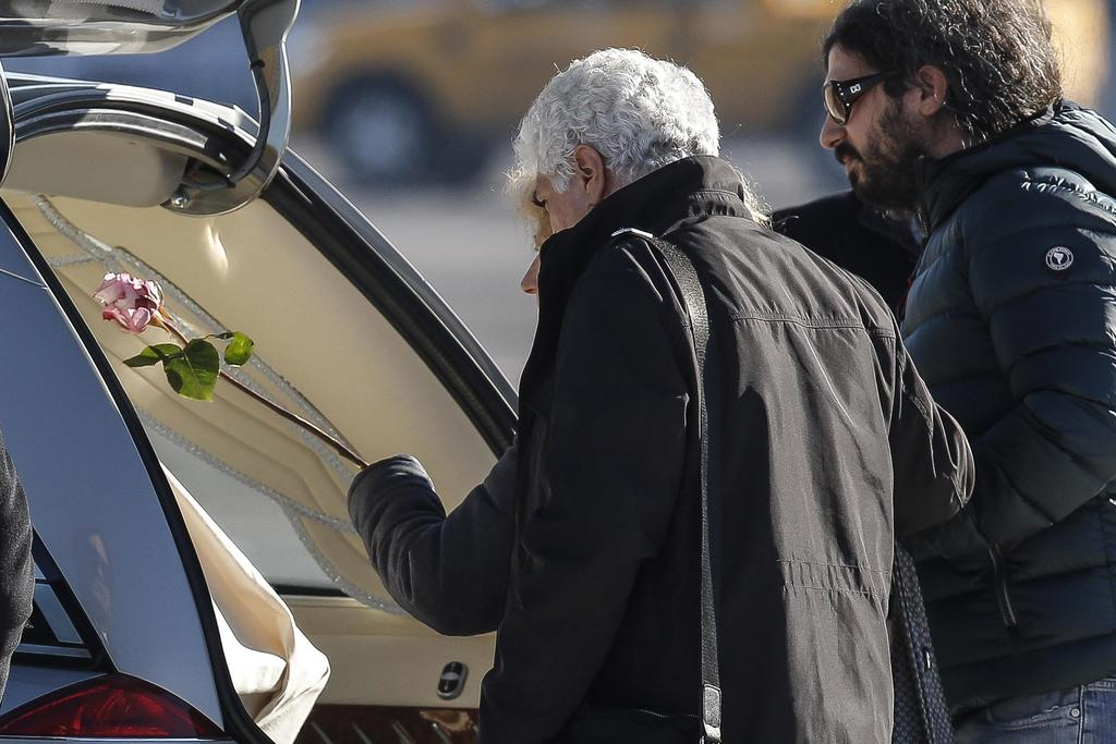 Giovanna Di Agostino, flanked by her husband Gaetano, left, and her son Gerardo, places a rose on the coffin of her daughter Italian vi...