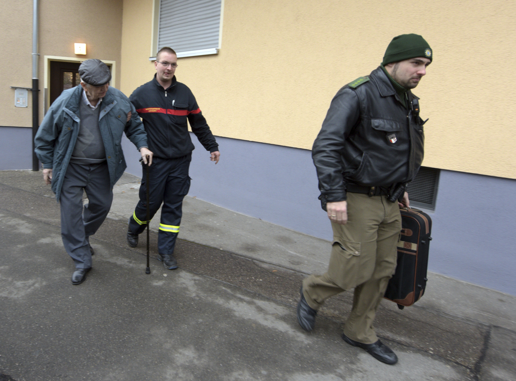 Police help a man to leave his apartment  in Augsburg, Germany, Sunday Dec. 25, 2016. Thousands of people in the German town of Augsbur...