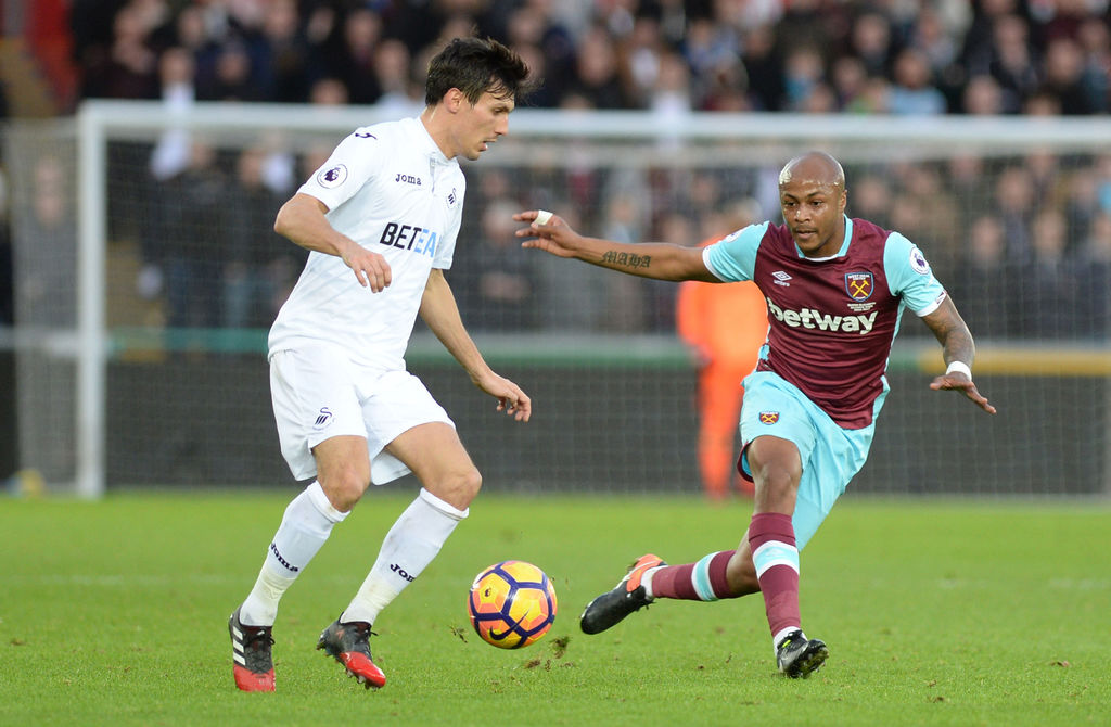 Swansea City's Jack Cork, left, and West Ham United's Andre Ayew in action during their English Premier League soccer match at the Libe...