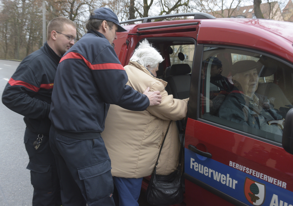 Rescuers help a woman into a car of the fure brigade after she left her home in Augsburg, Germany, Sunday, Dec. 25, 2016. Thousands of ...