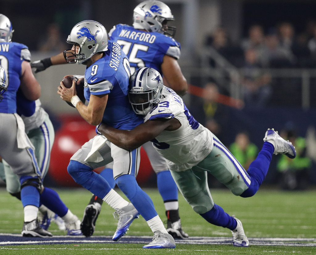 Detroit Lions quarterback Matthew Stafford (9) is sacked by Dallas Cowboys defensive end Benson Mayowa in the second half of an NFL foo...