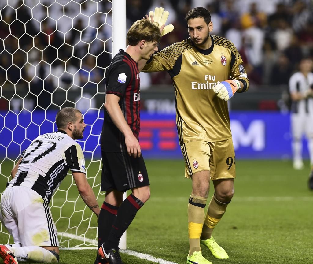 AC Milan goalkeeper Gianluigi Donnarumma, right, congratulates teammate Ignazio Abate as Juventus's Stefano Sturaro looks on, during th...