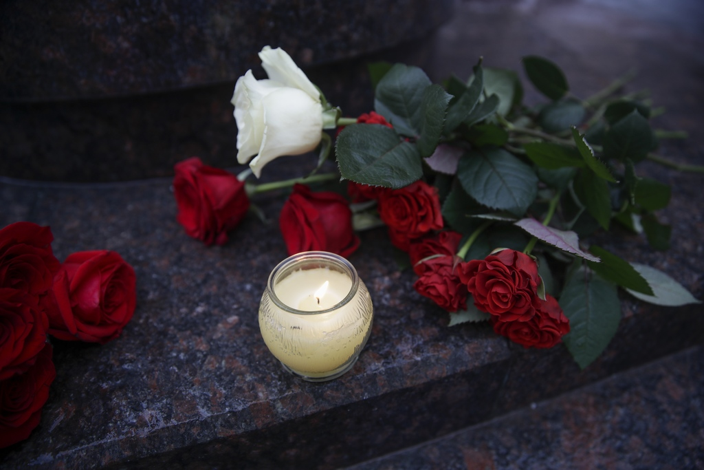 Flowers and candles are placed at the well-known military choir's building in Moscow, Russia, Sunday, Dec. 25, 2016, after a plane carr...