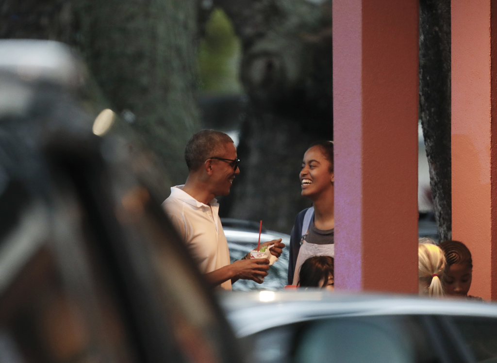 President Barack Obama laughs with his daughter Malia as they eat shave ice in front of Island Snow Hawaii in Kailua, Hawaii, Saturday,...