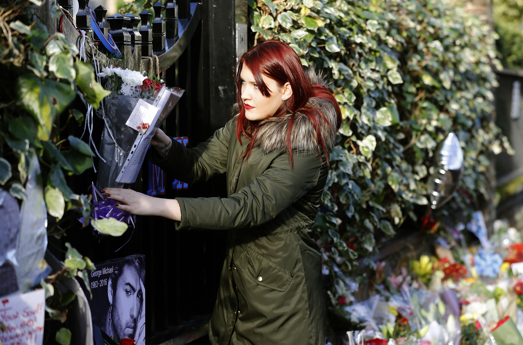 A woman hangs flowers at the entrance gate outside the home of British musician George Michael in London, Tuesday, Dec. 27, 2016. Georg...