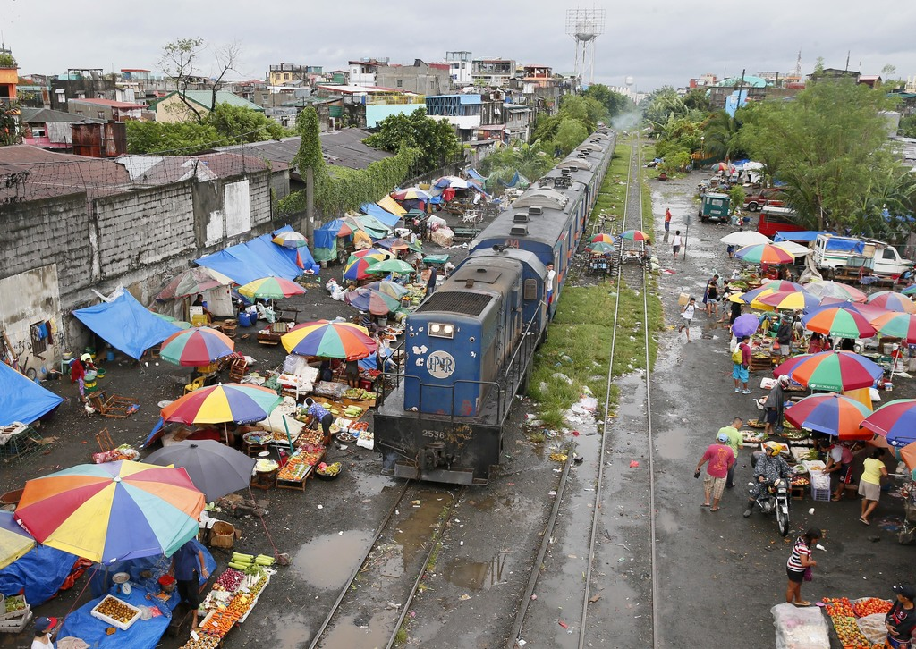 People go on their daily business despite intermittent rains brought about by typhoon Nock-Ten,  a day after Christmas Monday, Dec. 26,...