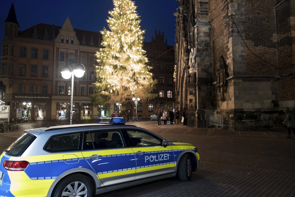 In this Dec. 24, 2016 picture a police car stands near the Market Church in Hannover, Germany, as security was tightened on Christmas E...