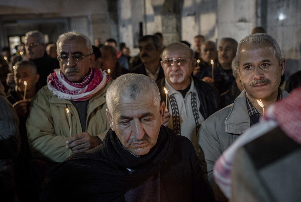 Iraqis attend Christmas Eve's Mass in the Assyrian Orthodox church of Mart Shmoni, in Bartella, Iraq, Saturday, December 24, 2016. For ...