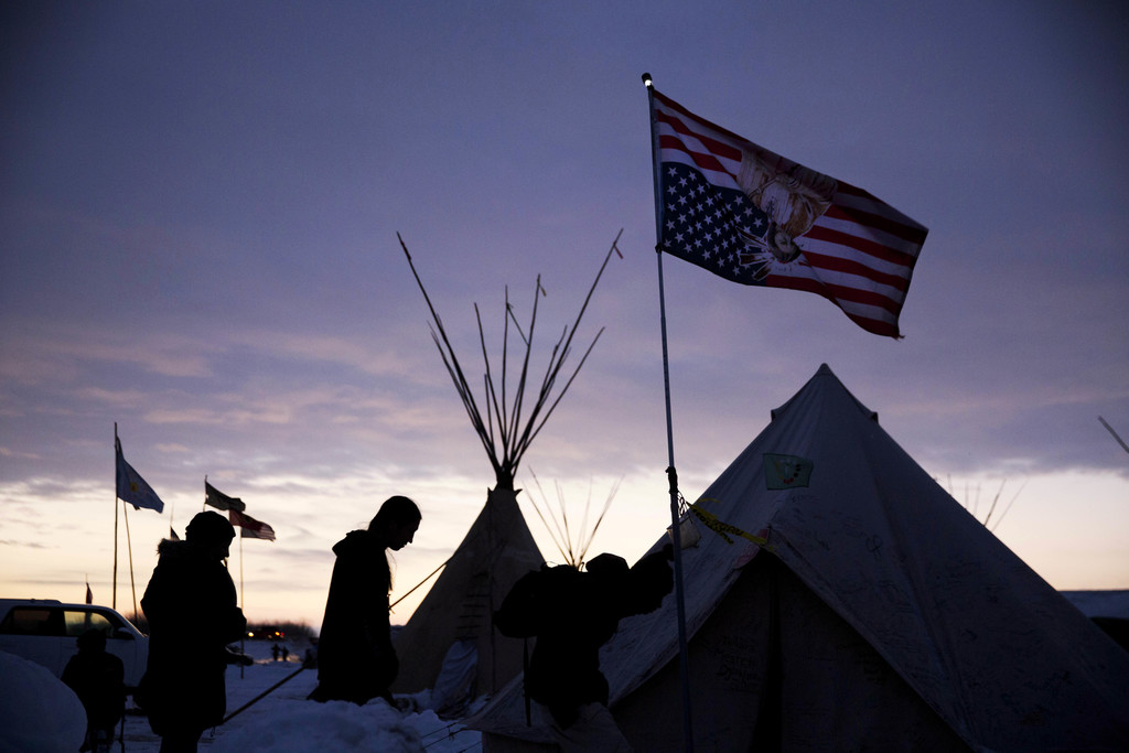 FILE - In this Dec. 2, 2016, file photo, travelers arrive at the Oceti Sakowin camp where people have gathered to protest the Dakota Ac...