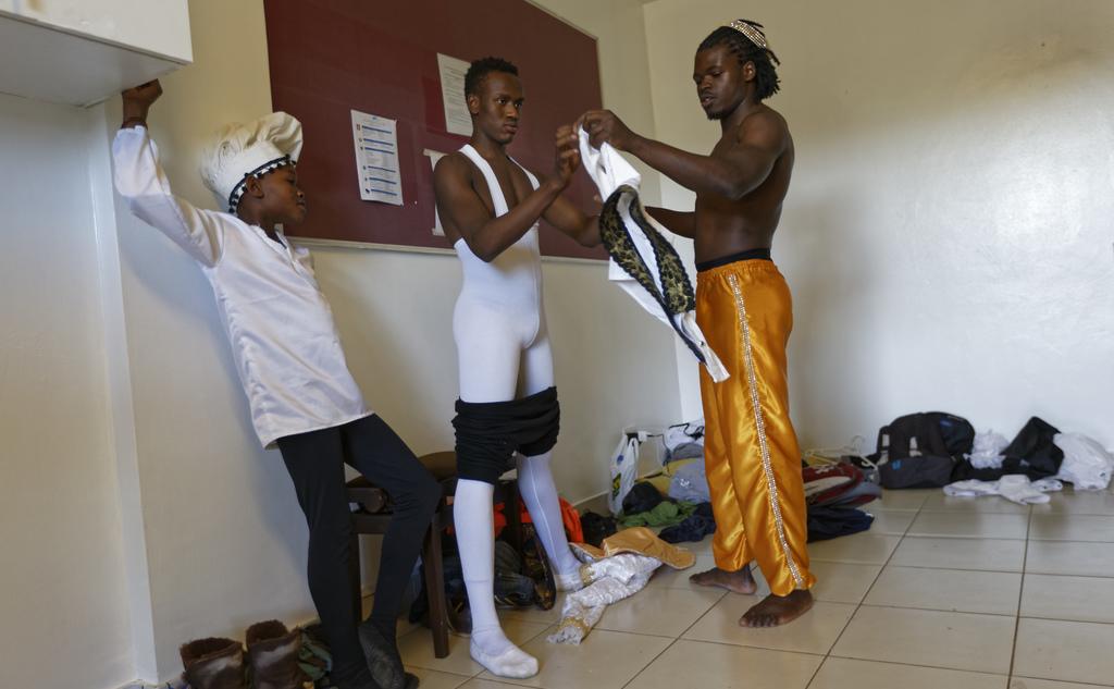 In this photo taken Friday, Dec. 9, 2016, Kenyan ballet dancer Joel Kioko, 16, center, is helped to put on his costume by dance teacher...