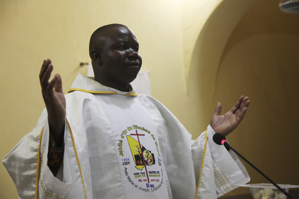 In this photo taken Saturday, Dec. 24, 2016, Anthero Afeku, a Catholic priest performs a mass to celebrate Christmas at Philippe Amore ...