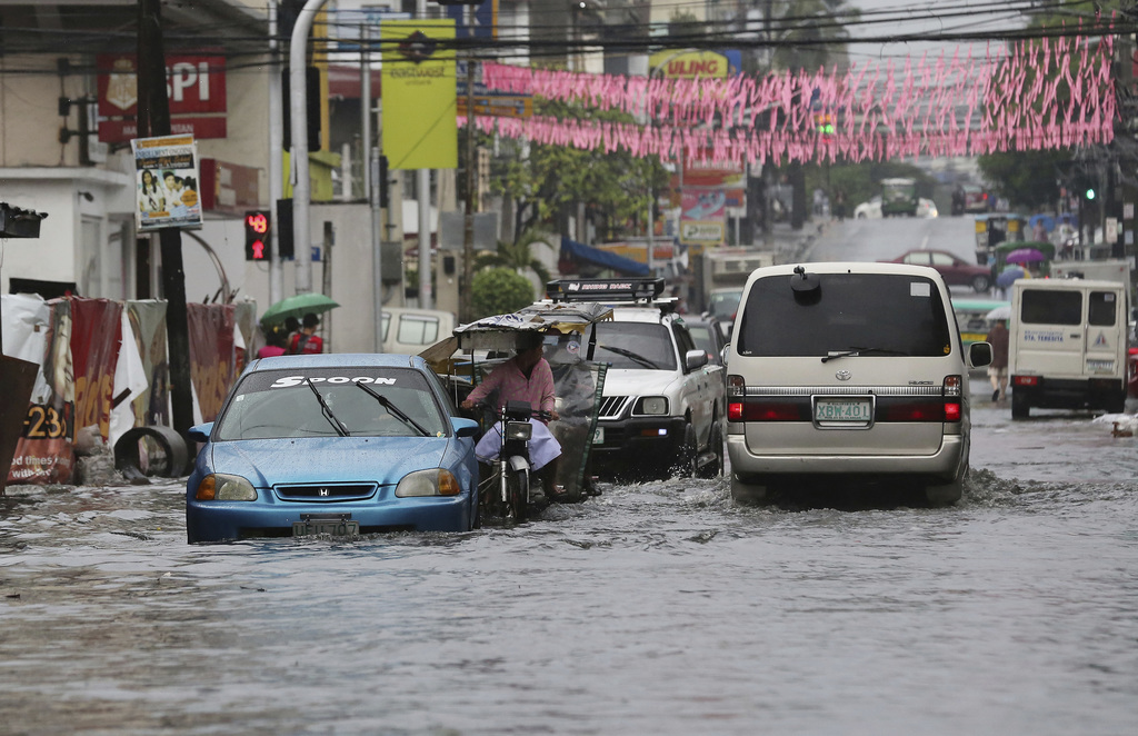 Vehicles navigate a flood-prone area caused by rains from Typhoon Nock-Ten in Quezon city, north of Manila, Philippines on Monday, Dec....