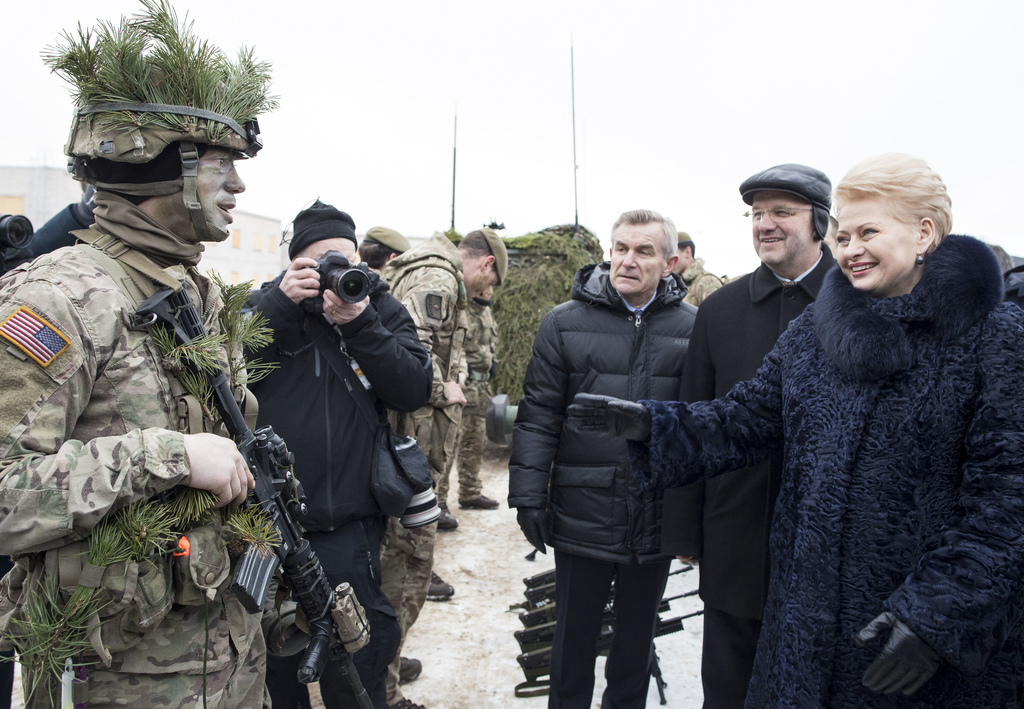 FILE - In this Friday, Dec. 2, 2016 file photo, Lithuanian President Dalia Grybauskaite, right, speaks with a soldier from the US Army,...