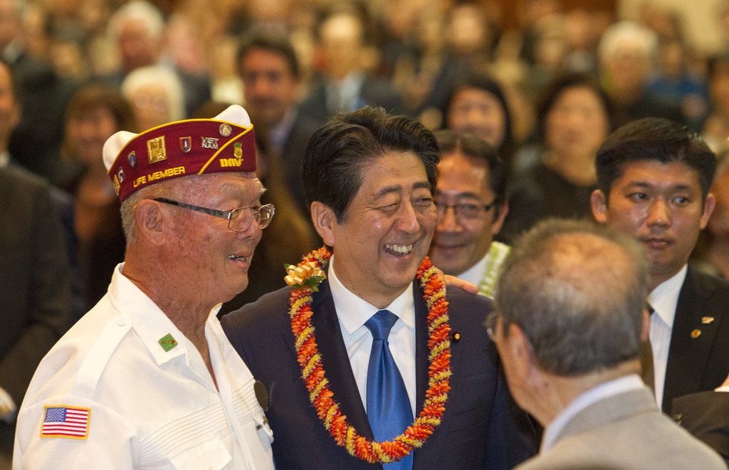 Japanese Prime Minister Shinzo Abe, center, greets guests at a dinner held in Abe's honor, Monday, Dec. 26, 2016, in Honolulu. Abe laid...