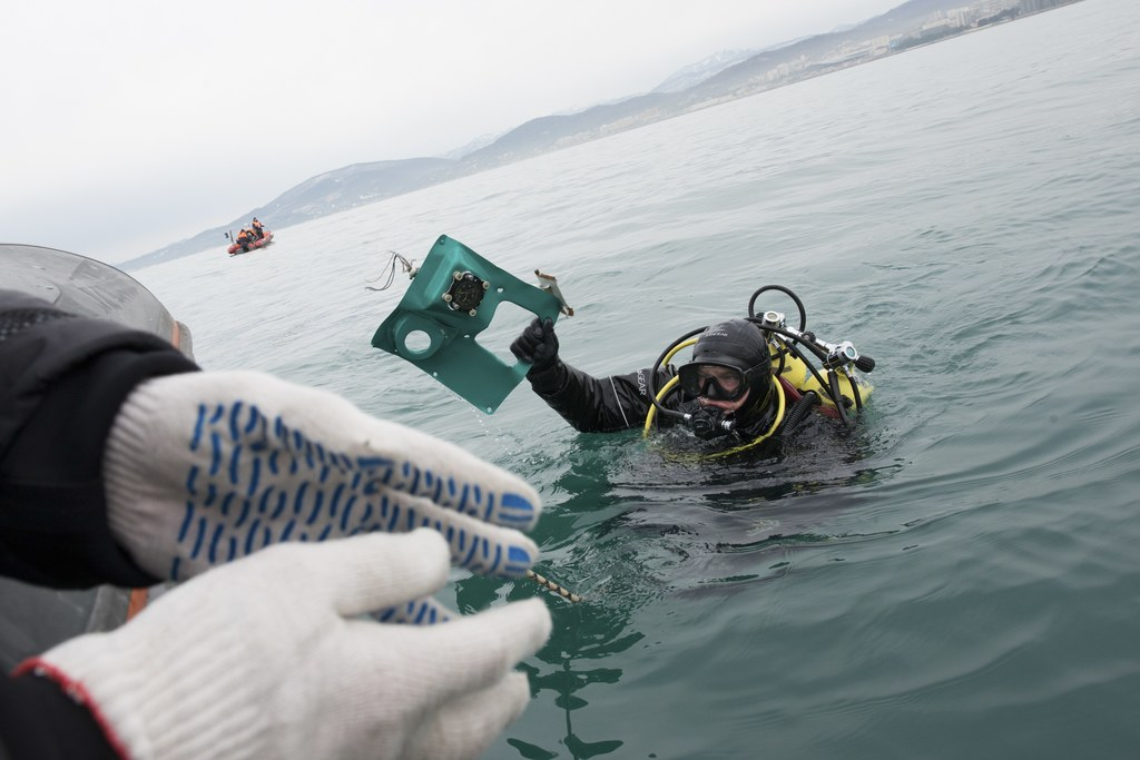 A Russian Emergency Ministry diver lifts a fragment of a plane in the Black Sea, outside Sochi, Russia, Tuesday, Dec. 27, 2016. Investi...