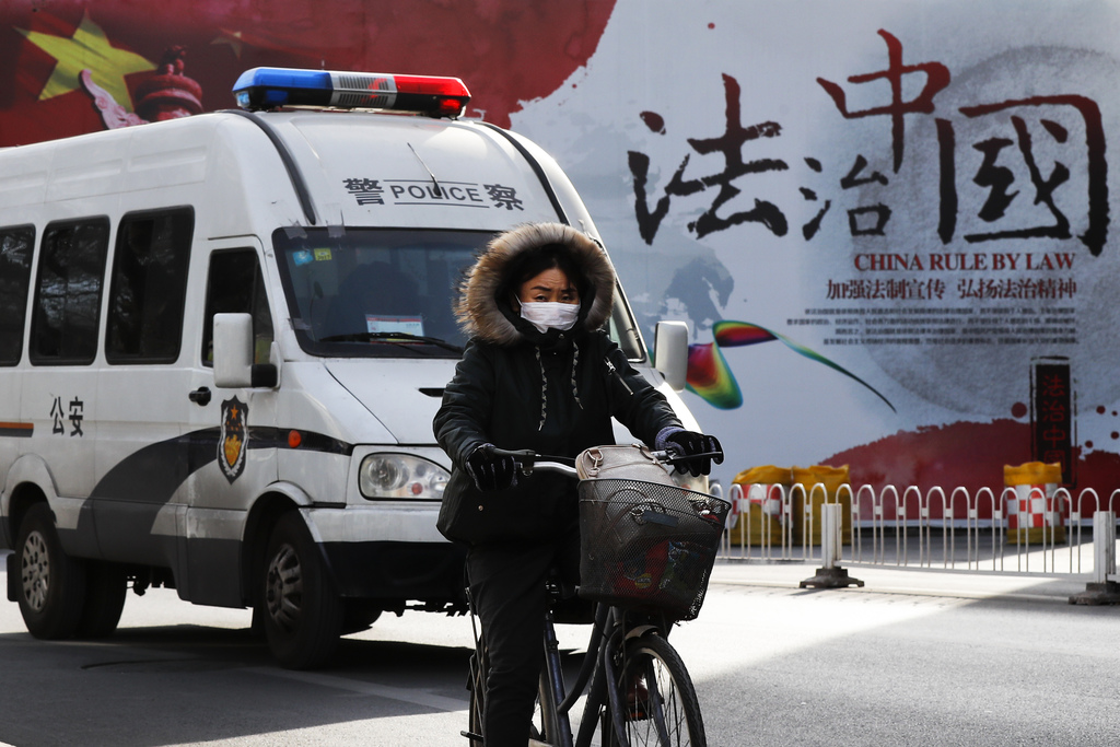 "A woman rides a bicycle in front of a police van as they pass a Chinese government's propaganda billboard that reads ""China Rule By Law..."
