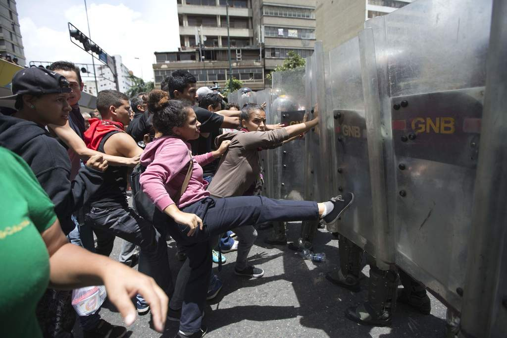 FILE - In this June 2, 2016 file photo, a woman kicks National Guard soldiers' shields during a protest demanding food, near Miraflores...