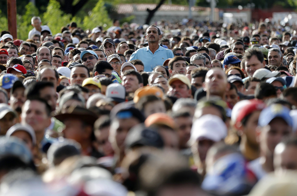 FILE - In this July 17, 2016 file photo, a man peaks over the crowd, waiting to cross the border into Colombia on the Simon Bolivar bri...