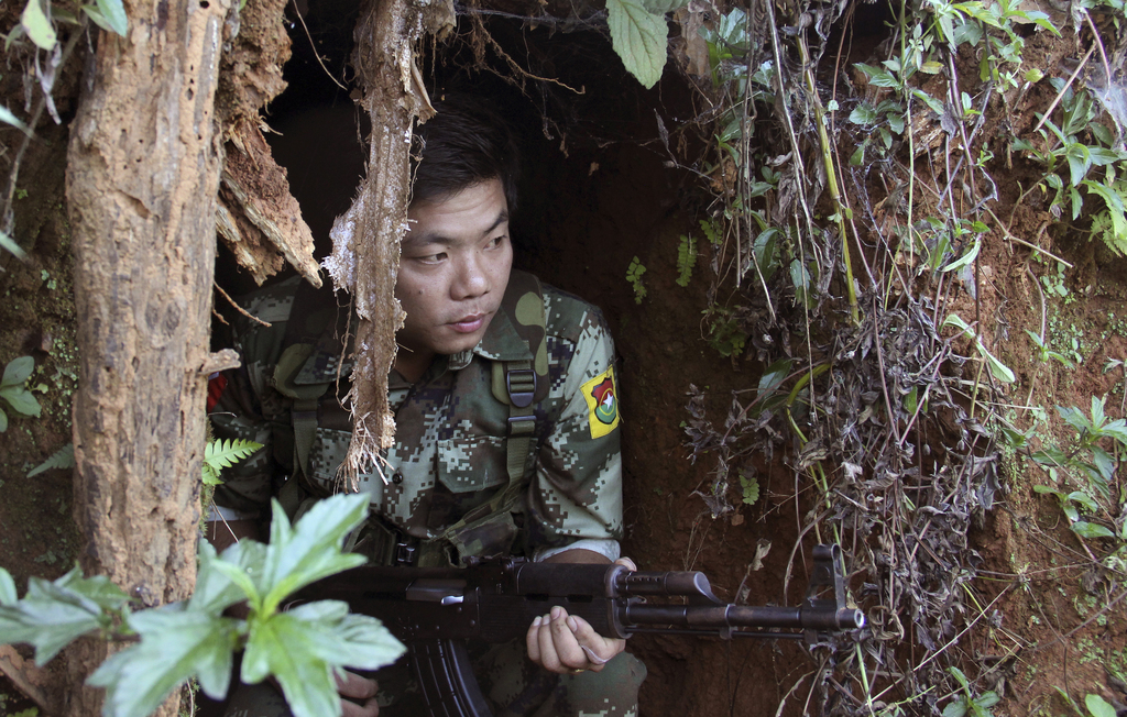 In this Nov. 30, 2016 photo, a Kachin Independence Army (KIA) soldier sits inside the bomb shelter along the bunker at the front line o...