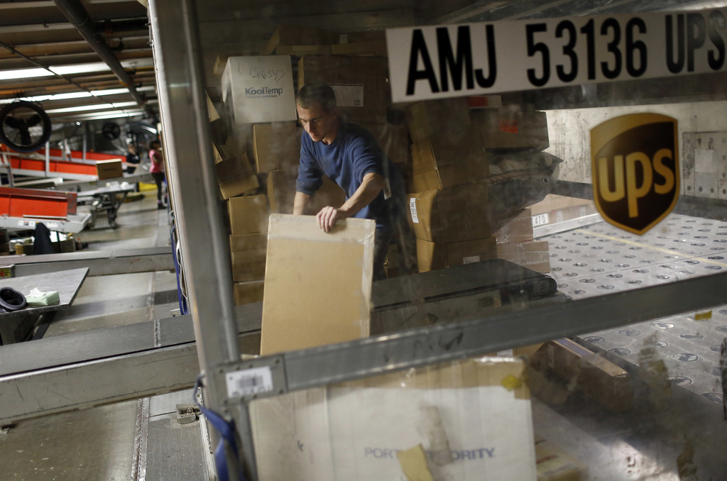 FILE - In this Nov. 20, 2015, file photo, UPS employee Justin Sims prepares to place a package on a conveyor belt while unloading a con...