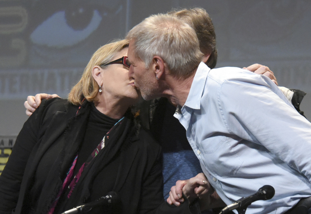 """FILE - In this July 10, 2015, file photo, Carrie Fisher, left, and Harrison Ford kiss at the Lucasfilm's """"Star Wars: The Force Awakens""""..."""
