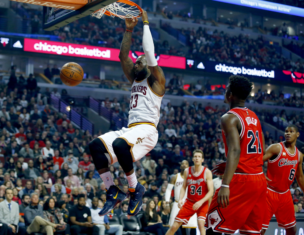 FILE - In this April 9, 2016 file photo, Cleveland Cavaliers forward LeBron James (23) hangs from the rim after dunking against the Chi...