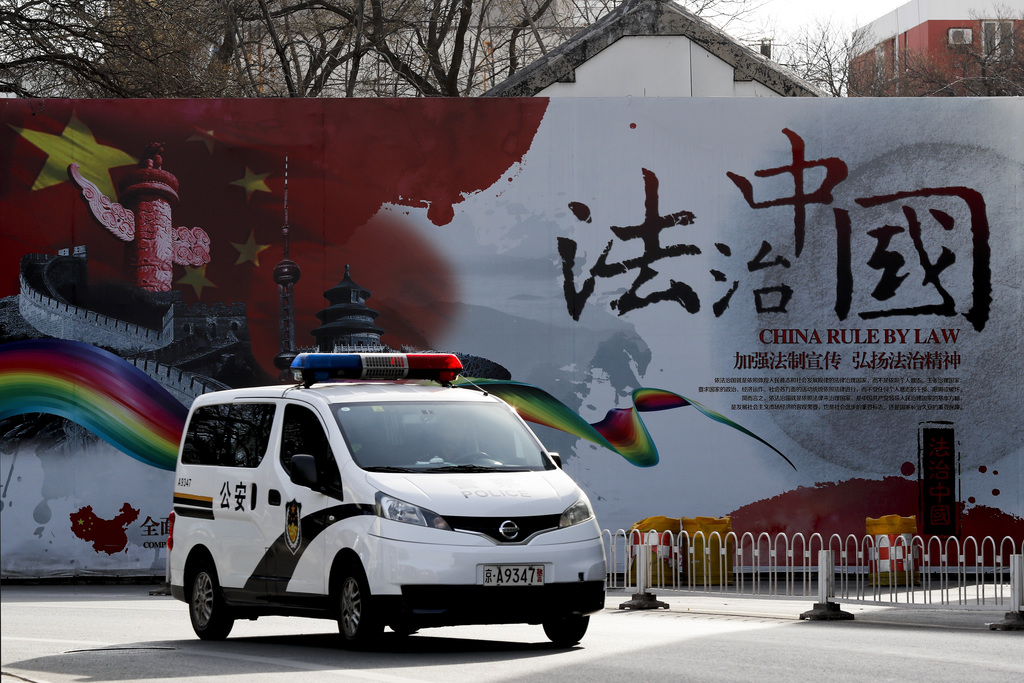 "A police car drives past a Chinese government's propaganda billboard reading ""China Rule By Law"" on a street in Beijing, Wednesday, Dec..."