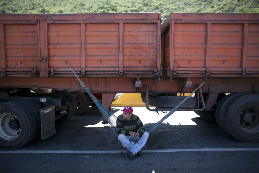 In this Nov. 14, 2016 photo, a truck driver rests on his hammock under his truck as he waits to enter the port in Puerto Cabello, Venez...