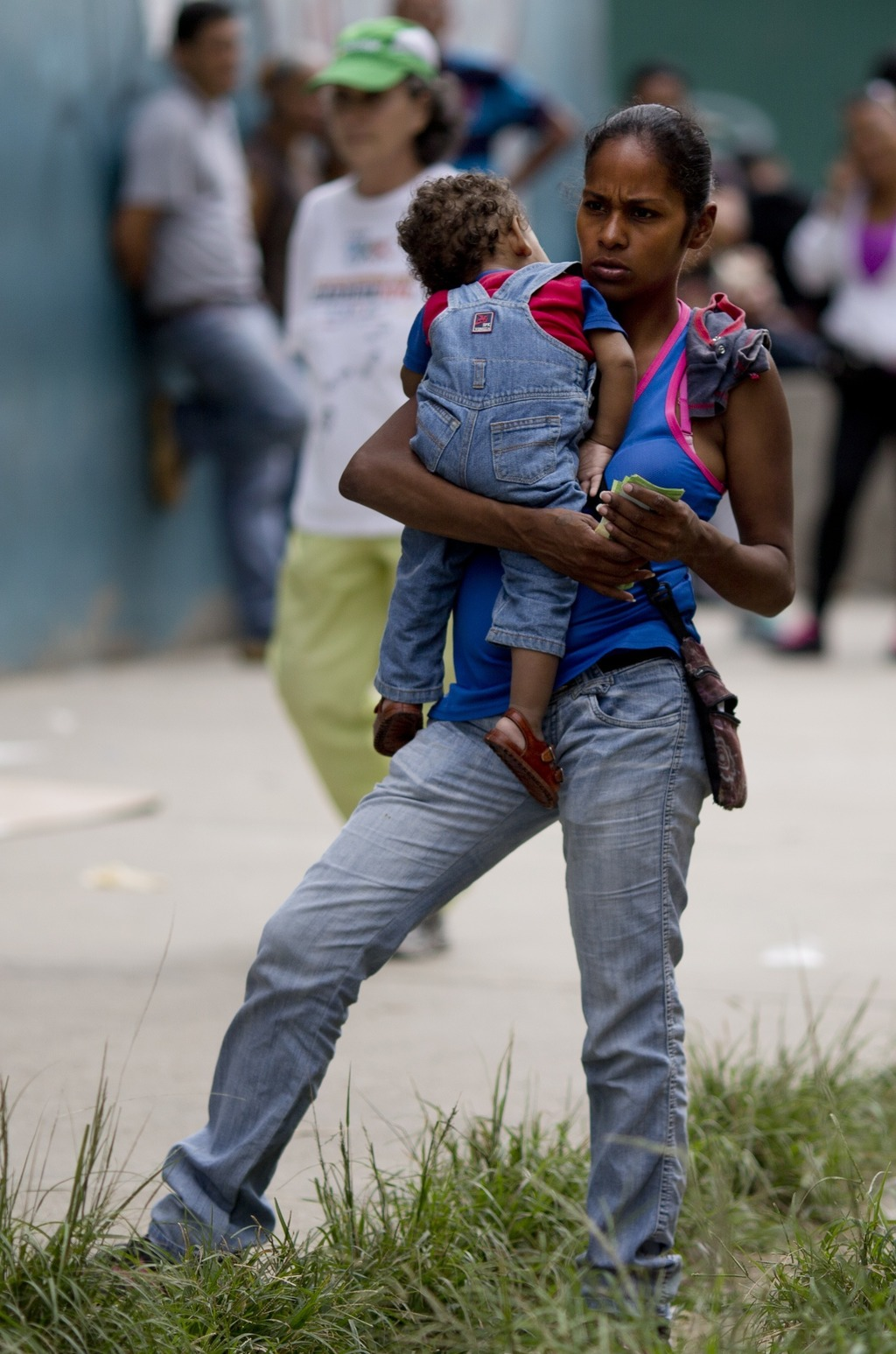In this Nov. 18, 2016 photo, a woman holding her baby waits outside a supermarket to buy government-subsidized food in Caracas, Venezue...