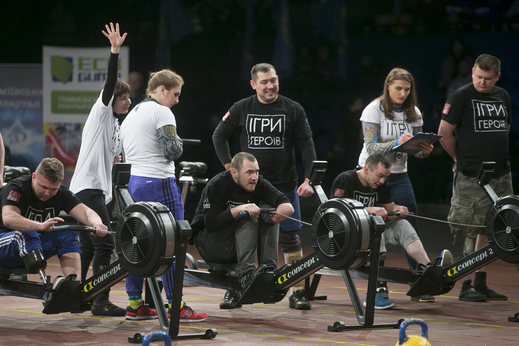 In this photo taken Saturday Dec.24, 2016, in Kiev, Ukraine, former servicemen perform strength exercises as judges watch, during the G...