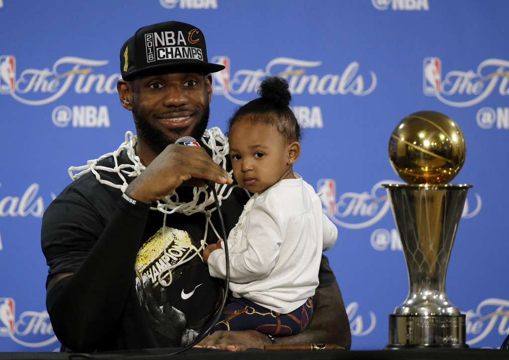 FILE - In this June 19, 2016 file photo, Cleveland Cavaliers' LeBron James answers questions as he holds his daughter Zhuri during a po...