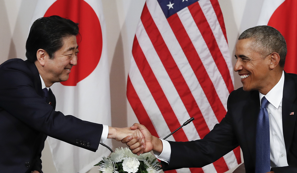 President Barack Obama and Japanese Prime Minister Shinzo shake hands as they are photographed at the start of a bilateral meeting at C...