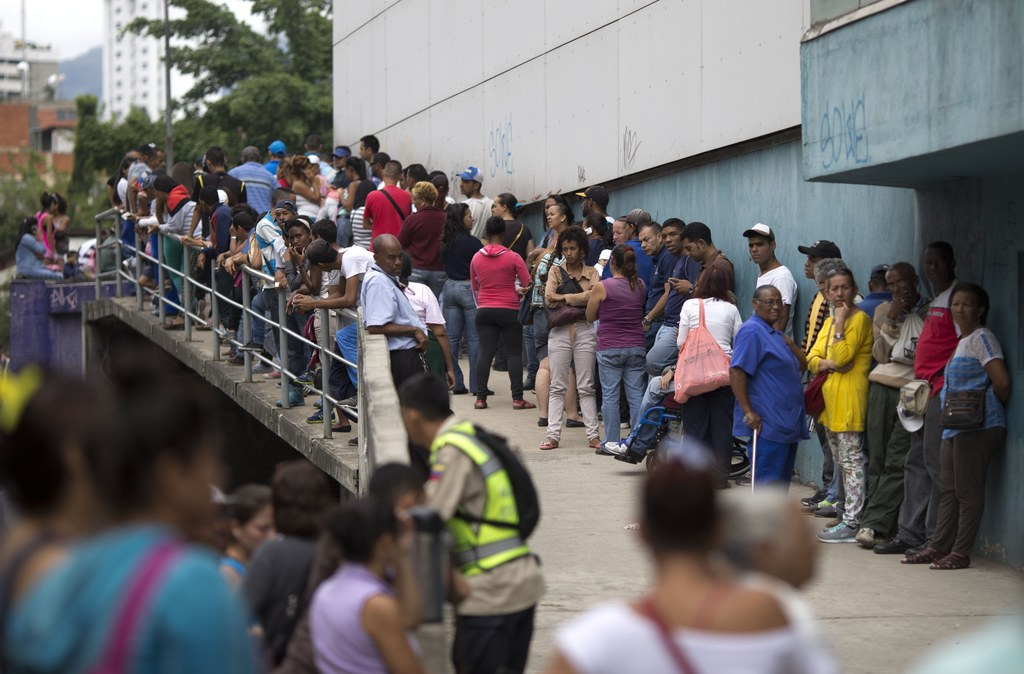 In this Nov. 18, 2016 photo, people wait outside a supermarket to buy government subsided food in Caracas, Venezuela. As domestic produ...