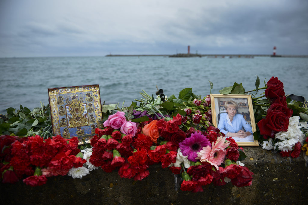 An icon and a portrait of Yelizaveta Glinka are placed among flowers at a pier in Sochi, Russia, in Sochi, Russia, Wednesday, Dec. 28, ...
