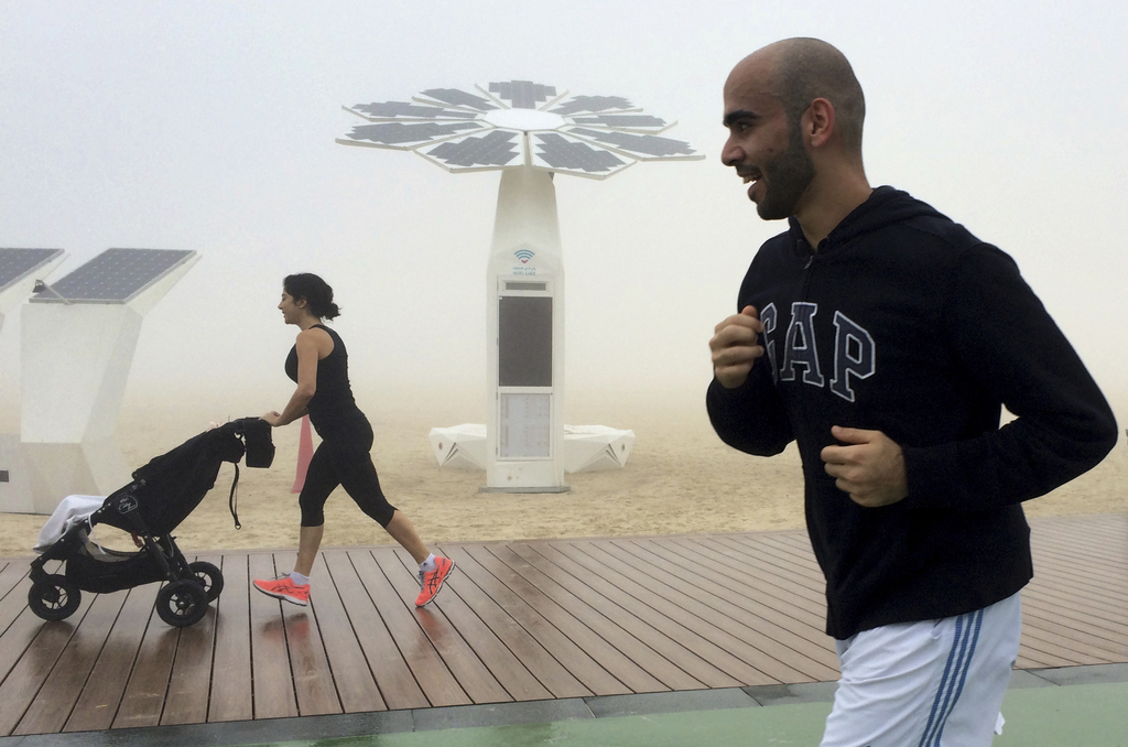 People jog at the Umm Suqeim beach on a foggy morning in Dubai, United Arab Emirates, Wednesday, Dec. 28, 2016. A heavy seasonal fog en...