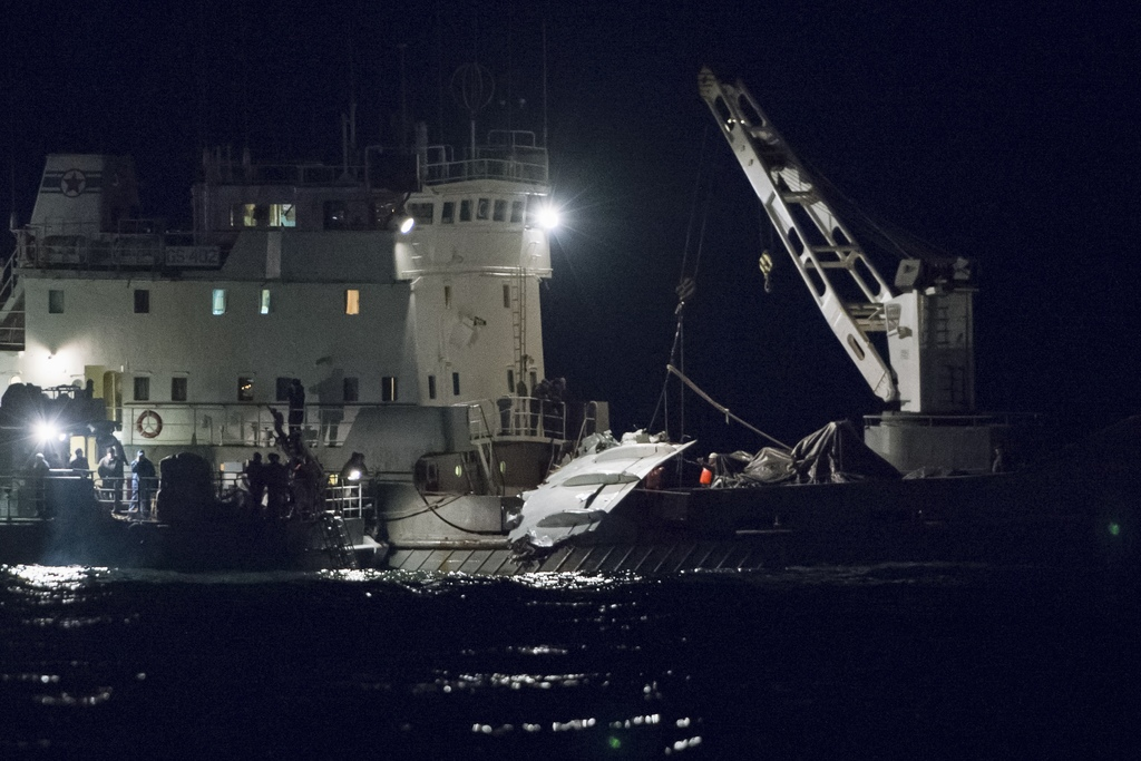 Russian Emergency Ministry employees lift a fragment of a plane in the Black Sea, outside Sochi, Russia, Tuesday, Dec. 27, 2016. Invest...