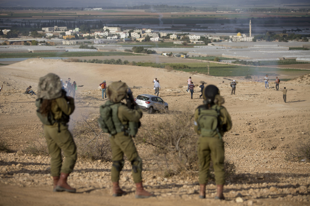 FILE -- In this Nov. 17, 2016 file photo, Palestinians and Israeli activists run away from a tear gas fired by Israeli soldiers during ...