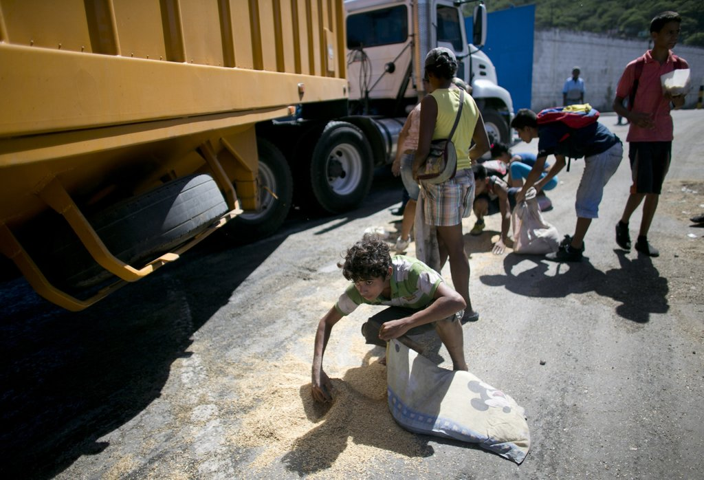 In this Nov. 14, 2016 photo, a youth uses his pillow as a bag to collect rice from the pavement that shook loose from a food cargo truc...