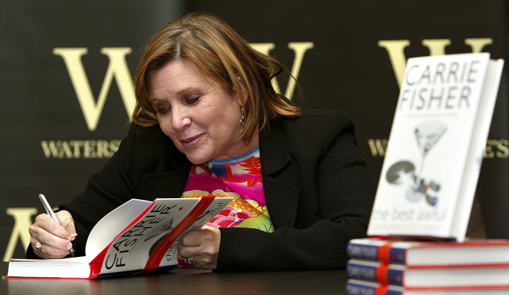 "FILE - In this Friday, Feb. 20, 2004 file photo, author Carrie Fisher autographs her new book ""The Best Awful"" at a promotional event i..."