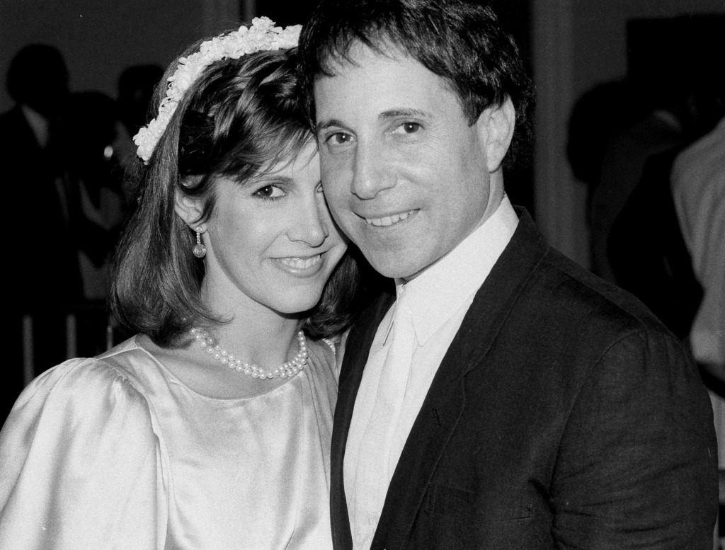 FILE - In this Tuesday, Aug. 16, 1983, file photo, actress Carrie Fisher and singer Paul Simon stand together at their apartment in New...