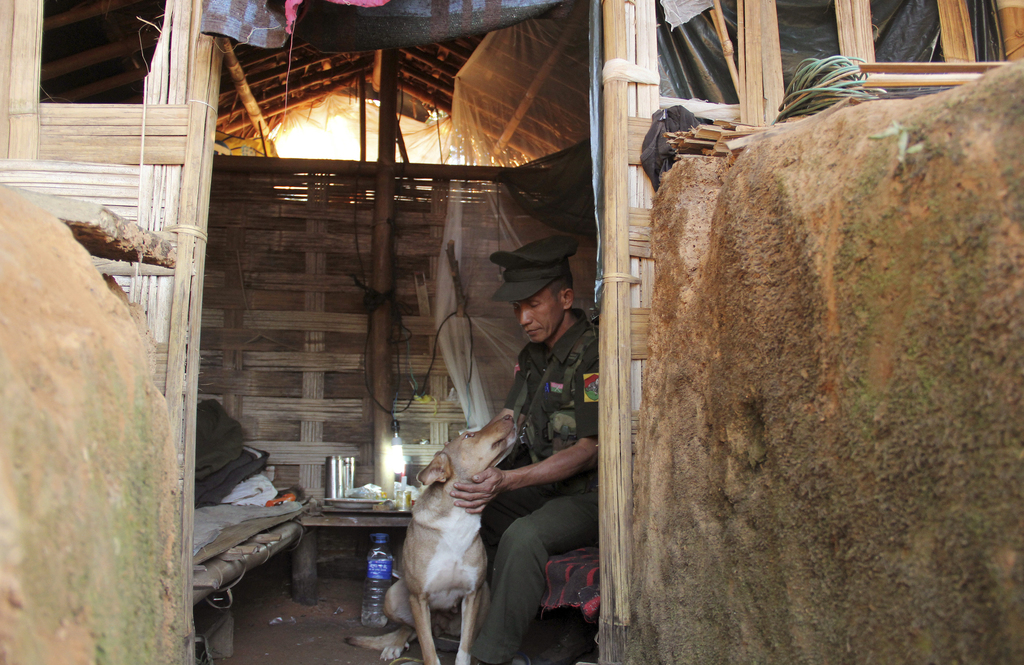 In this Nov. 30, 2016 photo, a Kachin Independence Army (KIA) soldier sits with his dog named 'English' inside a hut along the bunker a...