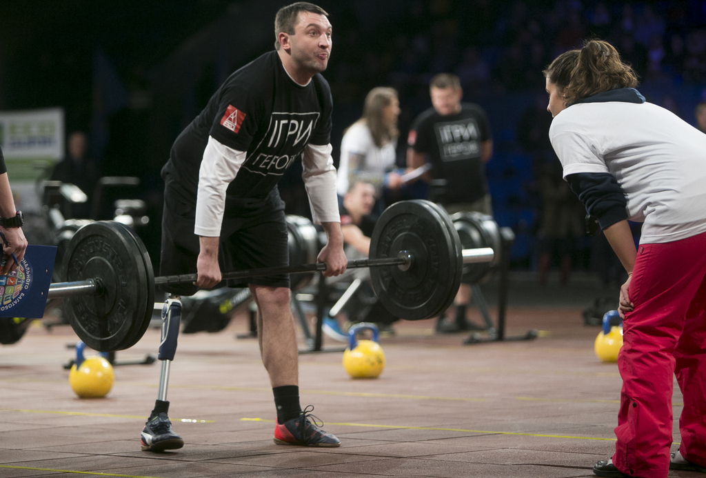 In this photo taken Saturday Dec. 24, 2016, a participant lifts weight as a judge watches, during the Games of Heroes CrossFit competit...