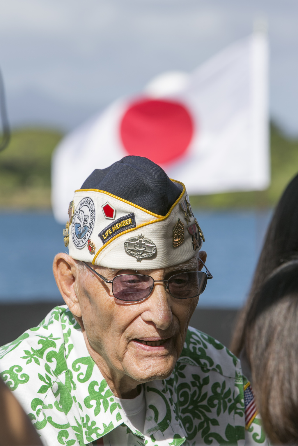 With the Japanese flag fluttering in the background, Pearl Harbor survivor Sterling Cale speaks to media at Joint Base Pearl Harbor Hic...