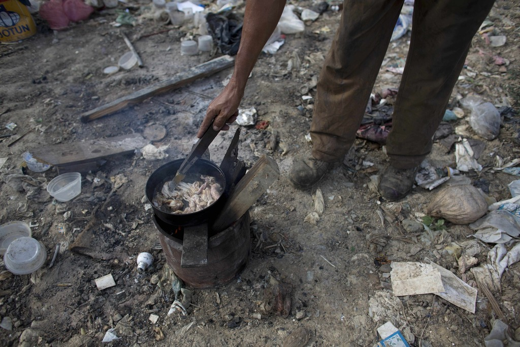 In this Nov. 1, 2016 photo, a man cooks chicken skin he found at the dump in Puerto Cabello, Venezuela, the port city where the majorit...